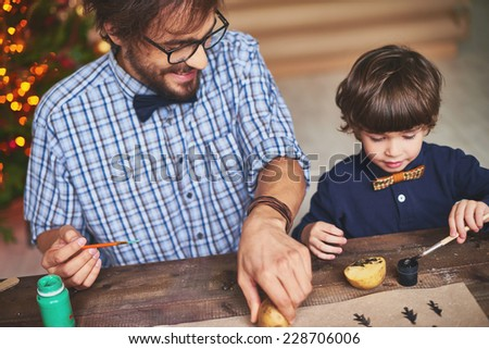 Happy father and son practicing potato printing on paper with black and green gouache - stock photo