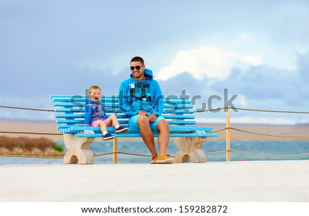 happy father and son relax on bench near the embankment - stock photo