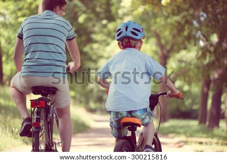 Happy father and son ride on bikes in summer park