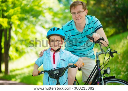Happy father and son ride on bikes in summer park - stock photo