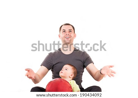 Happy father and son sitting on the floor with balloon - stock photo
