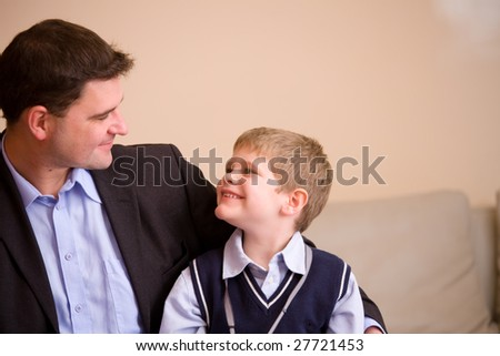 Happy father and son sitting together on couch at home, looking at each other, smiling. - stock photo