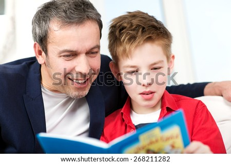 Happy father and son spending time in reading. Dad looking into the boys book - stock photo
