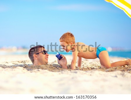 happy father and son talking on smart phone together, on the beach - stock photo