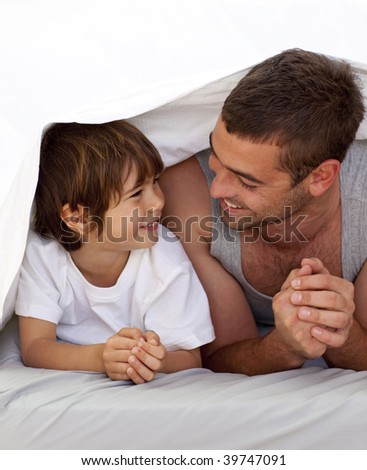Happy father and son talking under the bedsheets - stock photo