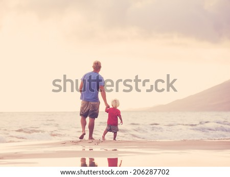 Happy father and son walking on the beach at sunset