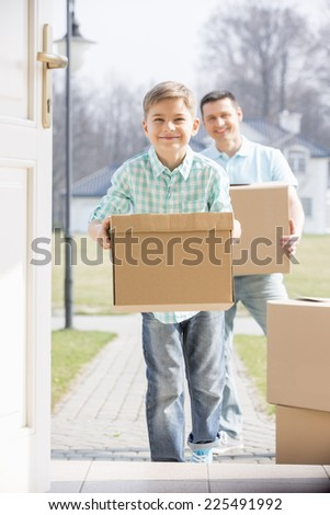 Happy father and son with cardboard boxes entering new home - stock photo