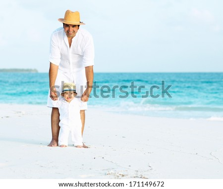 Happy father and son with panama hats on the tropical beach - stock photo
