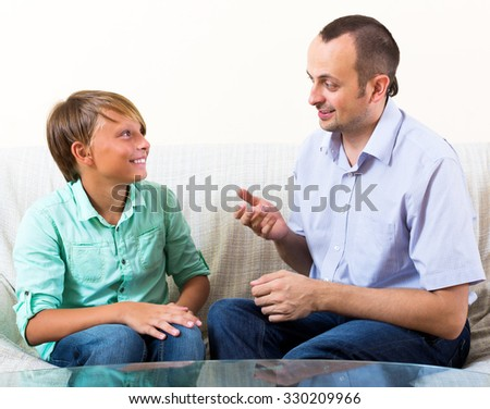 Happy father and teenage son discussing something interesting indoors - stock photo