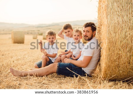 Happy father and three sons in the summer - stock photo