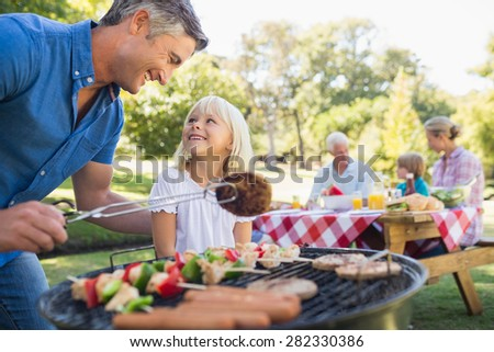 Happy father doing barbecue with her daughter on a sunny day - stock photo