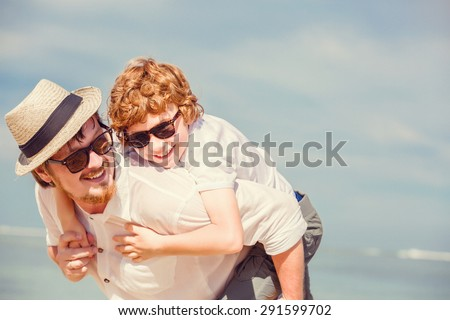 Happy father  father with beard and red haired son wearing sunglasses having happy summer time at a sunny day on vacation. Family, hapiness, travel concept - stock photo