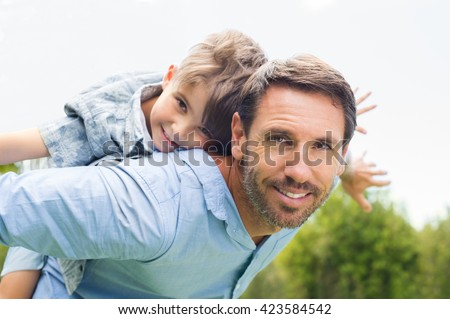 Happy father giving piggyback ride to his son and looking at camera. Happy kid riding piggyback on his father. Cute boy flying on father. 