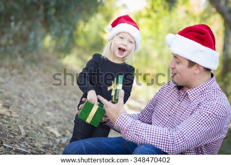 Happy Father Giving Young Daughter A Christmas Gift Outdoors. - stock photo