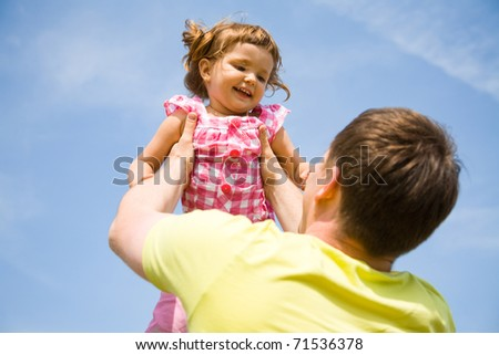 Happy father has a good summer time with his little daughter background on the blue sky - stock photo