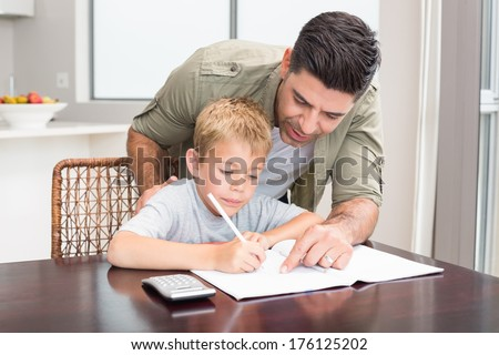 Happy father helping son with math homework at table at home in kitchen - stock photo