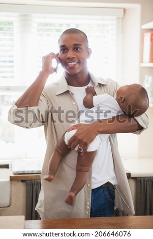 Happy father holding baby son while talking on phone at home in the kitchen - stock photo