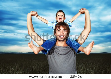 Happy father holding his little son in the wheat field over beautiful cloudy sky. - stock photo