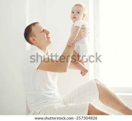 Happy father holding on hands his baby at home in white room near window - stock photo