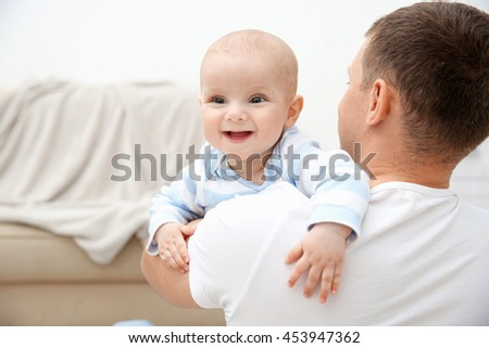 Happy father holding sweet baby in the room