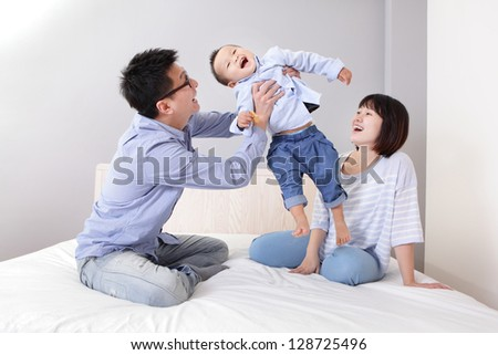 happy father hug his son with smile mother sitting on bed at home, asian family - stock photo