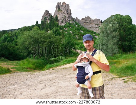 Happy father is carrying his baby in the comfortable knapsack. Dad is holding cute little baby boy. Man and (child) kid are smiling and enjoying nature. Caucasian male model. Summer day. Outdoors. - stock photo