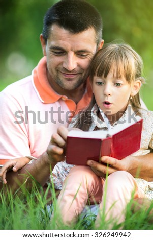 happy father is reading interesting book to his daughter outdoors - stock photo