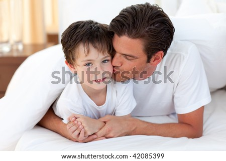 Happy Father kissing his son lying on bed - stock photo