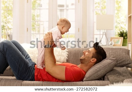 Happy father lying on sofa holding baby girl, playing, smiling. Side view.