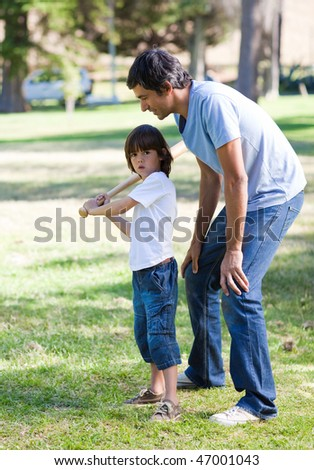 Happy father playing baseball with his son in the park - stock photo