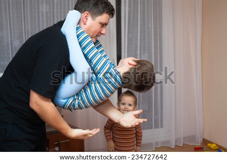 Happy father playing with his child boy at home - stock photo