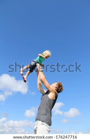 Happy father playing with his laughing toddler daughter - stock photo