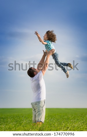 Happy father playing with kid in green spring field against blue sky