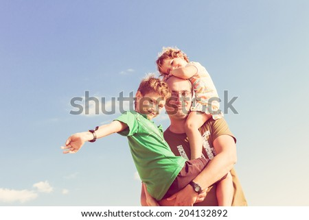 happy father playing with two kids outdoors - stock photo