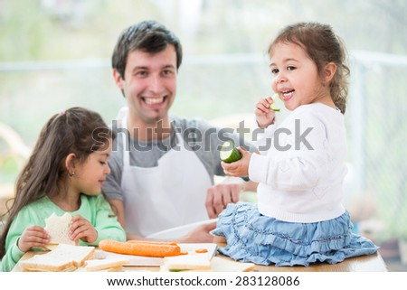 Happy father preparing sandwiches while daughters eating at home - stock photo