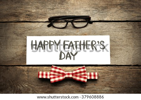 Happy Father's Day inscription with red bow tie and glasses on wooden background. Greetings and presents - stock photo