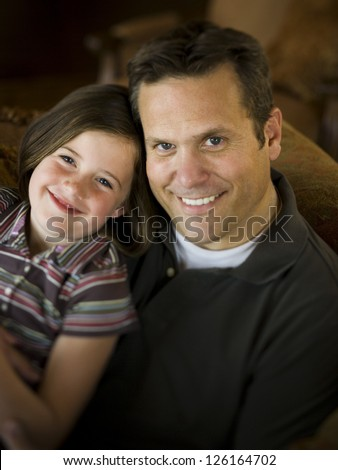 Happy father sitting with his daughter at home
