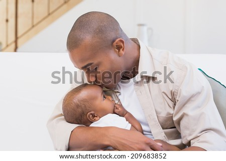 Happy father spending time with baby on the couch at home in the living room - stock photo
