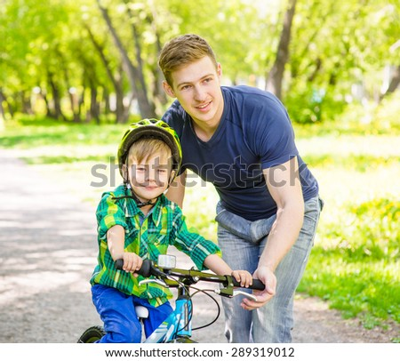 happy father teaches his son to ride a bike - stock photo