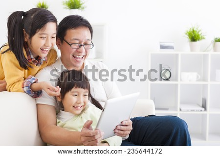 happy father using tablet pc with little girls - stock photo
