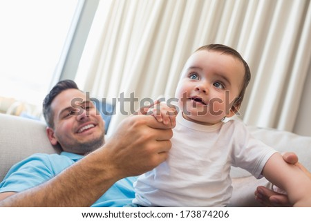 Happy father with cute baby boy at home - stock photo
