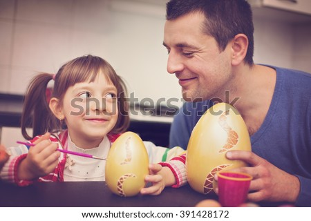 Happy father with daughter painting eggs for Easter - stock photo
