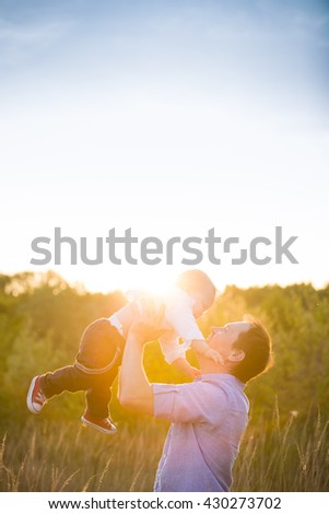 Happy father with his adorable toddler boy son on sunset. Father holding cute baby in the sky on sunny day. Family having fun and enjoying day in the park. Fatherhood, childhood and lifestyle concept - stock photo
