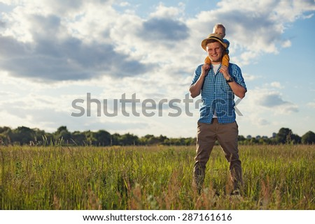 happy father with his baby son on his neck - stock photo