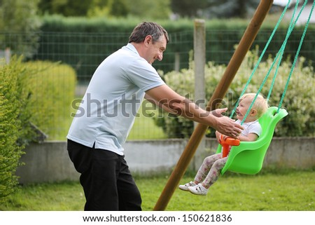 Happy father with his cute baby daughter playing with swing in the garden at backyard of the house - stock photo
