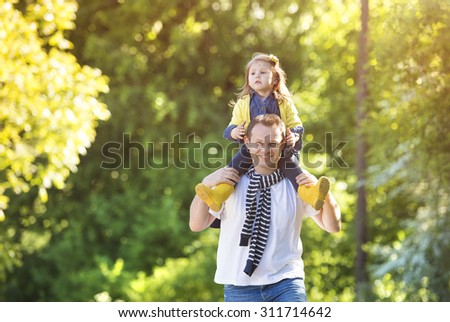 Happy father with his daughter spending time together outside in green nature       - stock photo