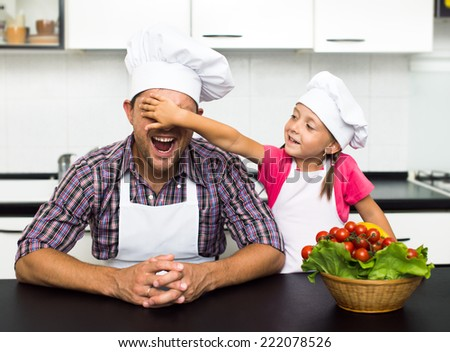 happy father with his little daughter  preparing a salad in their kitchen - stock photo