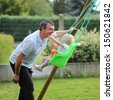 Happy father with his lovely baby daughter playing with swing in the garden at backyard of the house - stock photo