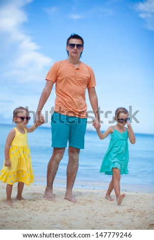 Happy father with his two daughters walking on tropical beach vacation - stock photo