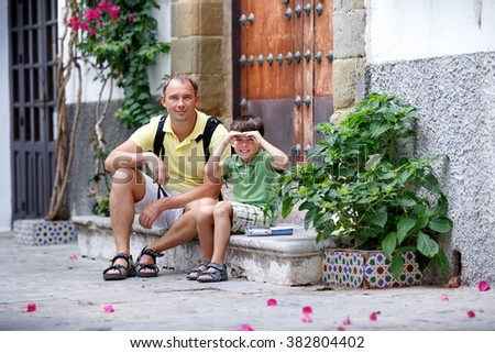 Happy father with son having rest outdoors in city on beautiful summer day